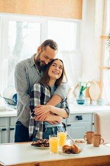 Liefdevolle man knuffelen zijn mooie vriendin in de keuken. ontbijt voor hun neus