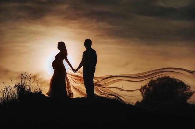 Liefdevolle man knuffelt een zwangere vrouw bij zonsondergang, tegen de achtergrond van de zee, rivier, staande op de pier. portret van mooie pasgetrouwden die een baby verwachten. fotografie, concept.