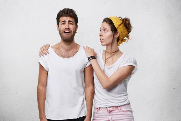 Liefdevolle, meelevende en zorgzame vrouw die haar trieste, huilende echtgenoot in tranen troost, steunt en troost, probeert hem op te vrolijken, de handen op zijn schouders houdt, hem psychologische steun geeft
