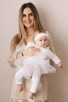 Liefdevolle moeder die haar pasgeboren baby thuis draagt. helder portret van een gelukkige moeder die een slapend kind op handen houdt. moeder knuffelt haar zoontje van 4 maanden.