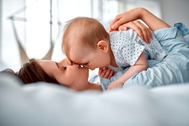 Liefdevolle moeder die haar pasgeboren baby thuis koestert. moeder en babyjongen spelen in zonnige slaapkamer. ouder en klein kind ontspannen thuis. familie plezier samen. kinderopvang, kraamconcept.