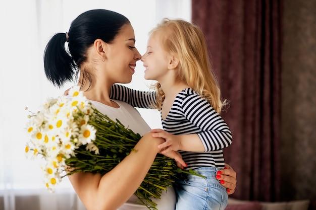 Liefdevolle moeder en dochtertje thuis met een boeket madeliefjes. de familie heeft het gezellig samen.