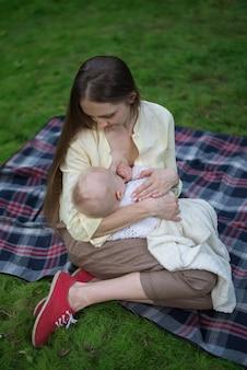 Liefdevolle moeder haar baby knuffelen en borstvoeding. picknick in het park met pasgeboren.