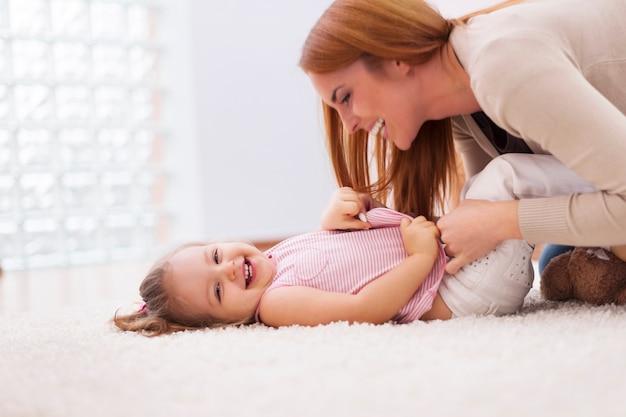 Liefdevolle moeder haar kleine meisje op tapijt thuis kietelen