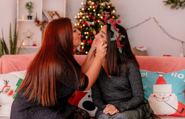 Liefdevolle moeder houdt haar dochter wangen zittend op de bank genieten van kersttijd thuis