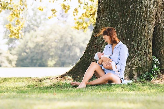 Liefdevolle moeder met haar pasgeboren baby op haar armen gelukkig moederschap en harmonieuze familie