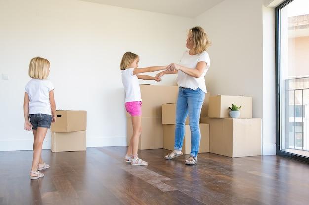 Liefdevolle moeder met plezier en dansen met kleuter dochter in nieuw huis