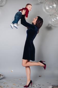 Liefdevolle moeder speelt met haar zoon die hem in handen opvoedt.