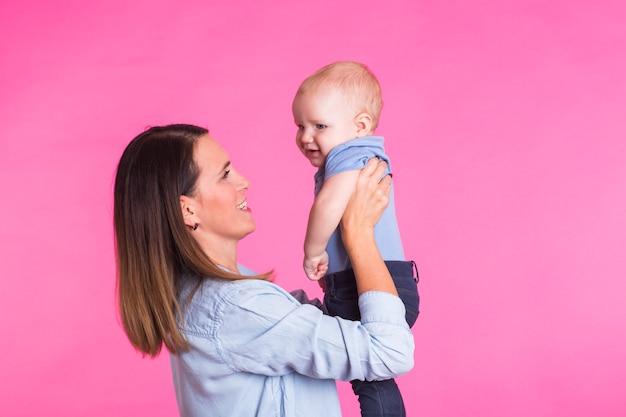 Liefdevolle moeder spelen met haar babyjongen op roze.