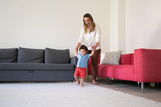 Liefdevolle moeder zoon handen vast te houden en hem te helpen lopen. grappig krullend gemengd ras jongetje leren lopen op tapijt op blote voeten en plezier binnenshuis. gezinsperiode, kindertijd en eerste stapconcept