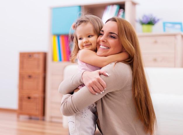 Liefdevolle omhelzende moeder en baby thuis
