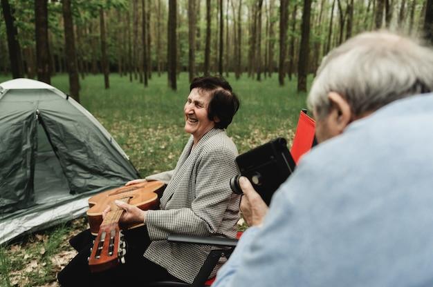 Liefdevolle ouder paar komen op picknick met gitaar. gelukkig hoger paar dat een gitaar speelt en een romantische date op kamp heeft.
