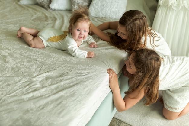 Liefdevolle oudere zussen spelen thuis met de engel van het broertje op het bed