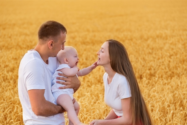Liefdevolle ouders en baby lopen door tarweveld. gelukkig jong gezin op het platteland.