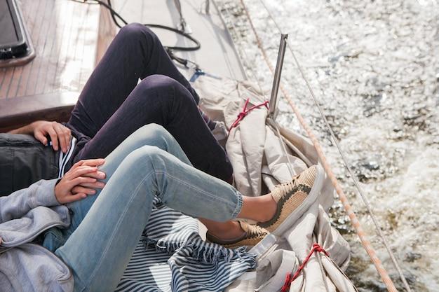 Liefdevolle paar hand in hand, liggend aan boord van het jacht tijdens een boottocht
