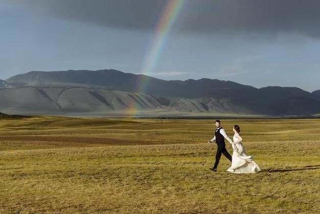 Liefdevolle paar jonggehuwden man bruidegom en vrouw bruid in trouwjurken lopen op een bergen en een regenboog
