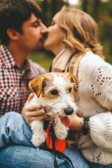 Liefdevolle paar kussen en knuffelen tijdens het wandelen met hun hond