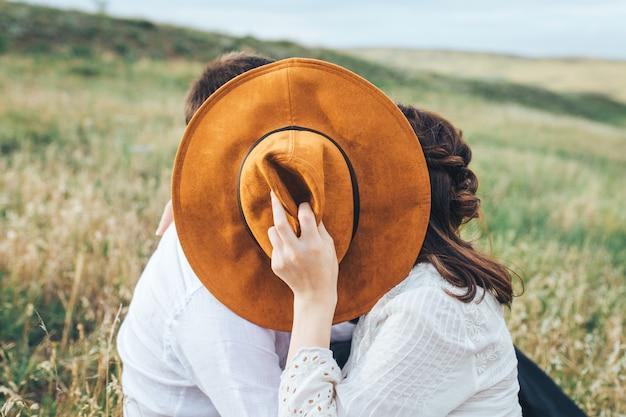 Liefdevolle paar kussen raken achter een hoed