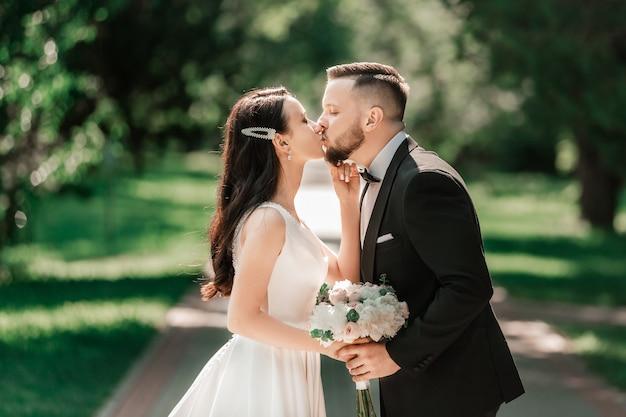 Liefdevolle paar pasgetrouwden staande op een park alley evenementen en tradities