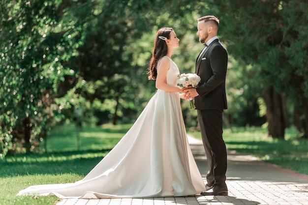Liefdevolle paar pasgetrouwden staande op een steegje in het park. evenementen en tradities
