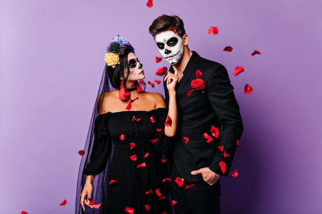 Liefdevolle paar vampiers poseren onder rode confetti. romantische zombies die koelen op halloween-feest.