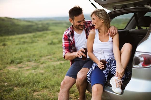 Liefdevolle paar zitten in de auto trank tijdens reis in de natuur