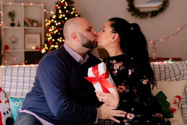 Liefdevolle romantische man en vrouw thuis in de kersttijd zittend op de bank in de woonkamer vrouw bedrijf geschenkpakket kussen op de lippen