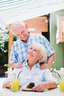 Liefdevolle senior koppel knuffelen in café op terras genieten van verfrissende drankjes