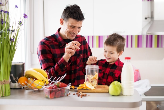 Liefdevolle vader en zoon in hetzelfde shirt maken een smoothie op het aanrecht gevuld met fruit.