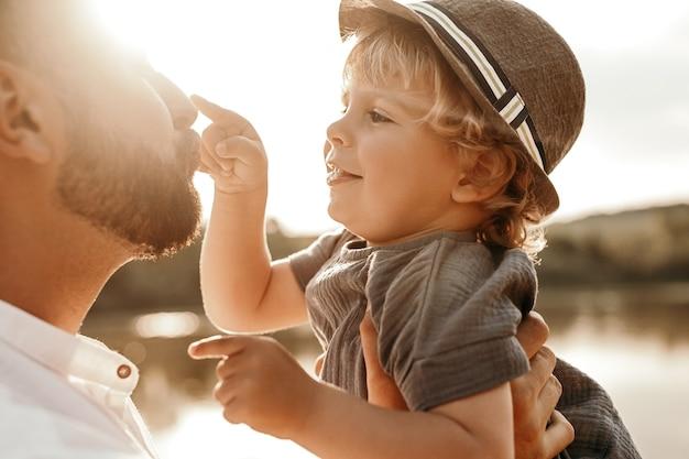 Liefdevolle vader en zoontje hebben plezier in de buurt van het meer
