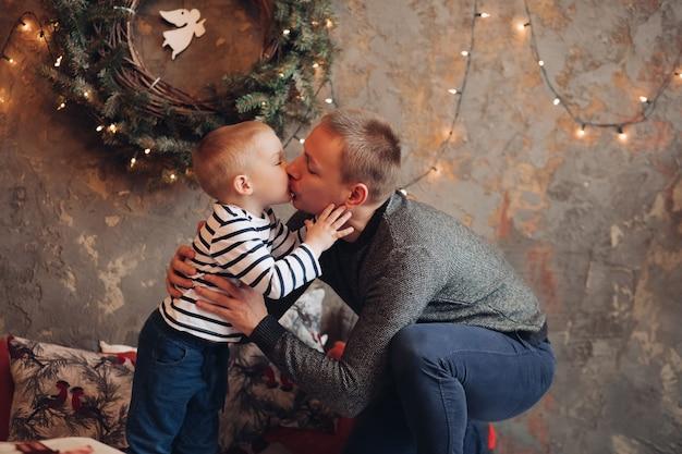 Liefdevolle vader kuste zijn zoontje en knuffelde hem tegen versierde muur met kerstkrans en slinger