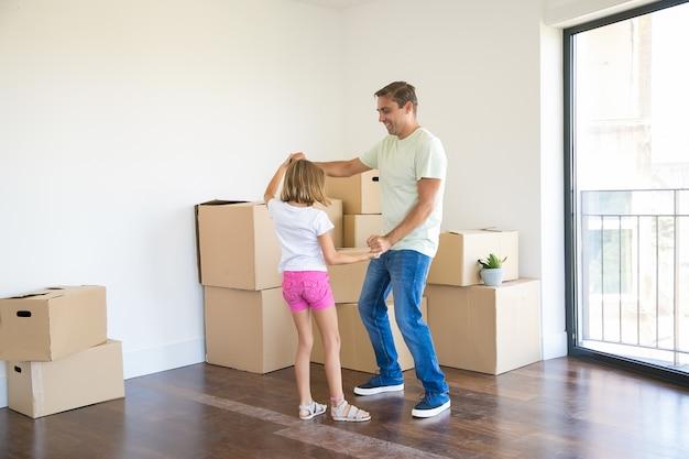 Liefdevolle vader met plezier en dansen met kleuter dochter in nieuw huis