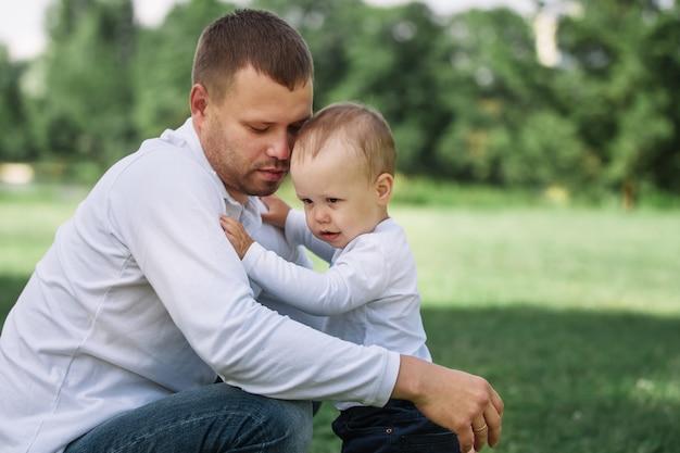 Liefdevolle vader praat met zijn jonge zoon terwijl hij buiten loopt