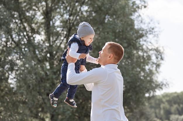 Liefdevolle vader speelt met zijn jonge zoon in het stadspark.