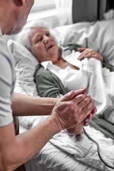 Liefdevolle volwassen man ter ondersteuning van zijn zieke vrouw liggend op bed, vrouw lijdt aan hoge druk, hartaanval.