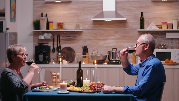 Liefdevolle volwassen paar verhogen champagne glas en roosteren terwijl u geniet van een romantisch diner thuis in de keuken. senior oude mensen eten de maaltijd, vieren hun jubileum in de eetkamer.