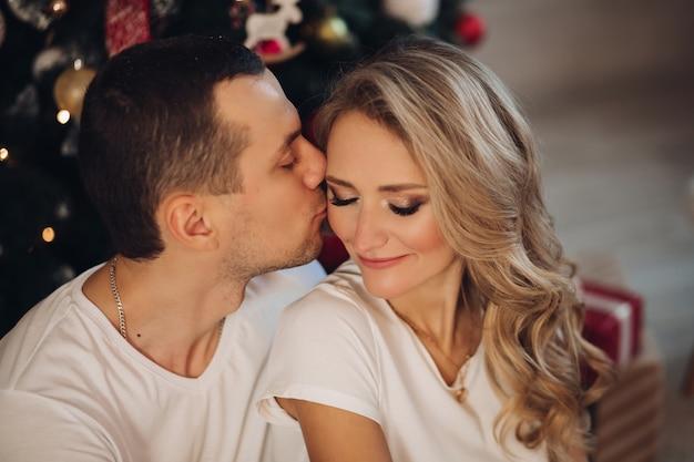 Liefdevolle vriendje kussende vriendin in de buurt van de kerstboom