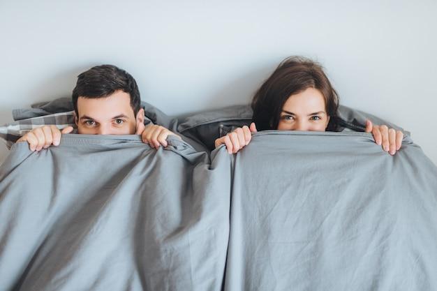 Liefdevolle vrolijke paar kijken uit deken, liggen samen op bed