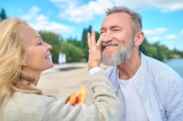 Liefdevolle vrouw met zonnebrandcrème en gelukkige man