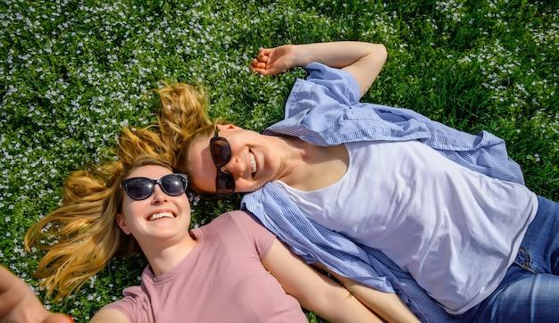 Liefdevolle vrouwelijke paar face to face liggend op bloeiende weide, rust, jeugd, unisex liefde, vriendschap