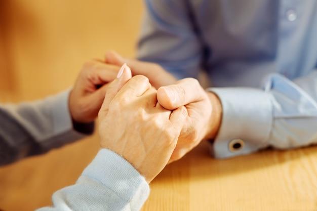 Liefdevolle zorgzame gelukkige toegewijde man en vrouw hand in hand en strelen hen
