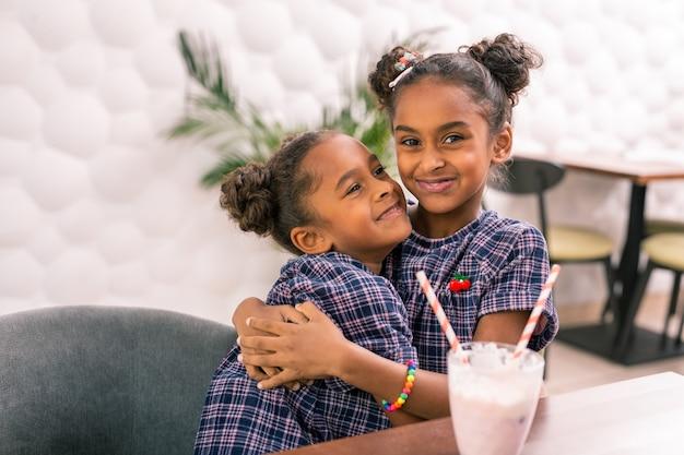 Liefdevolle zus. zorgzame, liefhebbende oudere zus die zich geweldig voelt terwijl ze haar schattige kleine zusje knuffelt in een vierkante jurk