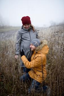 Liefdevolle zwangere paar lopen buiten de stad in de late herfst.