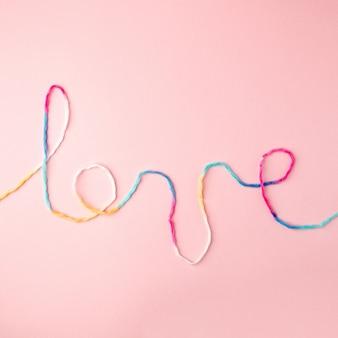 Liefdewoord met wollen draad het van letters voorzien, concept en achtergrond voor de dag die van valentine wordt geschreven