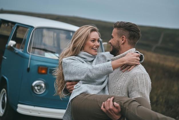Liefhebbend stel. knappe jonge man die zijn aantrekkelijke vriendin draagt en glimlacht terwijl hij buiten in de buurt van de blauwe retro-stijl minibus staat
