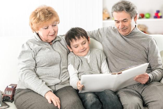 Liefhebbende grootouders met kleinkind zittend op de bank