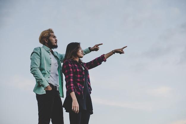 Liefhebbende hipsterpaar staande tegen duidelijke lucht. paar ontspannend vakantie concept.