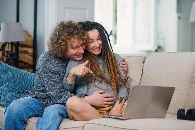 Liefhebbende man zit met zijn zwangere vrouw met stijlvolle dreadlocks op de bank en heeft videochat