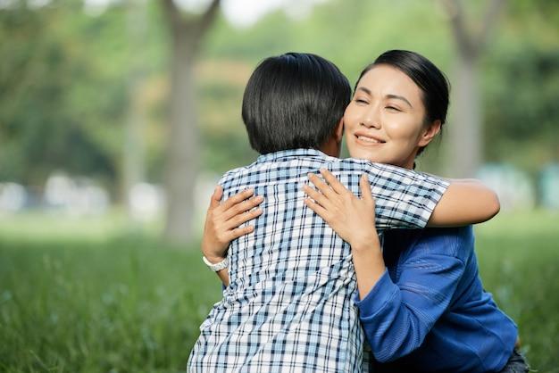 Liefhebbende moeder die zoontje omhelst
