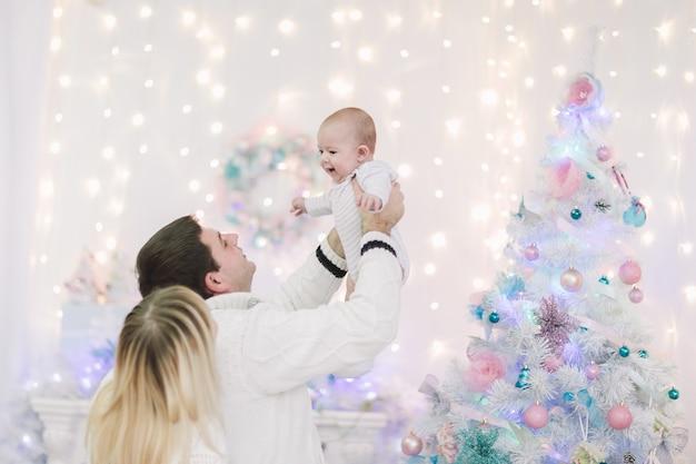 Liefhebbende ouders spelen met hun baby op kerstavond. het concept van gezinsgeluk